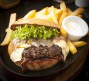 Hamburger. Large, abundant and tasty Hamburger with french fries royalty free stock image