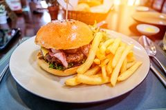 Beef burger with cheese and bacon served with french fried stock images