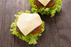 Hamburger with Lettuce and Cheese on wooden table Stock Images