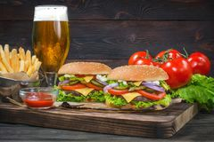 Hamburger and light beer on a pub background. royalty free stock image