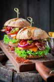 Hamburger made of bacon, tomato and beef. On wooden plank Royalty Free Stock Images