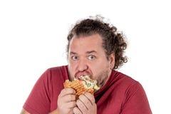 Hamburger mangiatore di uomini grasso divertente Gli alimenti a rapida preparazione, unhealty mangiano Sovrappeso e problemi sani fotografia stock