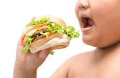 Hamburger in mano grassa obesa del ragazzo Fotografia Stock