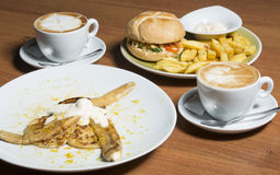 Hamburger meal and banana flambe dessert with coffee Royalty Free Stock Images