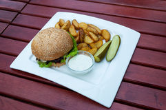 Hamburger meal. Served with baked potatoes at cafe Stock Photography