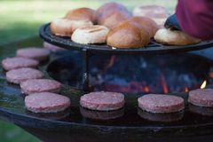 Hamburger meat and buns are grilled on the grill. Outside cooking and barbeque. Meal on the grill. Hamburger patties grilling outd. Oors on a fire barbecue grill stock image