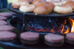 Hamburger meat and buns are grilled on the grill. Outside cooking and barbeque. Meal on the grill. Hamburger patties grilling outd. Oors on a fire barbecue grill stock photo