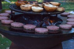 Hamburger meat and buns are grilled on the grill. Outside cooking and barbeque. Meal on the grill. Hamburger patties grilling outd. Oors on a fire barbecue grill royalty free stock photos