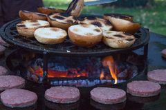 Hamburger meat and buns are grilled on the grill. Outside cooking and barbeque. Meal on the grill. Hamburger patties grilling outd. Oors on a fire barbecue grill royalty free stock images