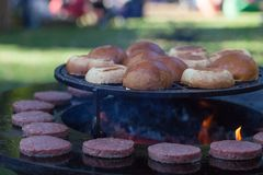 Hamburger meat and buns are grilled on the grill. Outside cooking and barbeque. Meal on the grill. Hamburger patties grilling outd. Oors on a fire barbecue grill royalty free stock photo