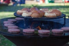 Hamburger meat and buns are grilled on the grill. Outside cooking and barbeque. Meal on the grill. Hamburger patties grilling outd. Oors on a fire barbecue grill royalty free stock photography