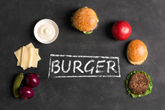 Hamburger with meat cutlet. Inscription of ingredients. Beef burger with lettuce and minced meat cutlet. Black chalkboard. Top view stock images