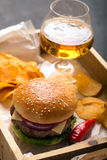 Hamburger with meat cutlet. Potato chips and beer Royalty Free Stock Photography