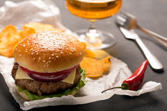 Hamburger with meat cutlet. Potato chips and beer Stock Photos