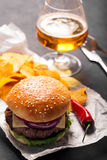 Hamburger with meat cutlet. Potato chips and beer Stock Photography