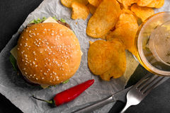 Hamburger with meat cutlet. Potato chips and beer Stock Image