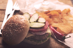 Hamburger with meat cutlet. Potato chips and beer Royalty Free Stock Images