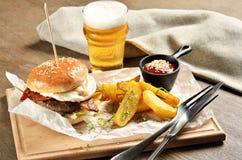 Hamburger, meksykańskie grule i ketchup na drewnianej desce, zdjęcia royalty free