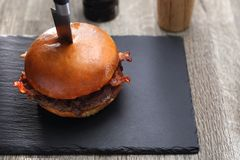 Hamburger met bacon Geroosterde rundvleeskotelet in een broodje stock fotografie