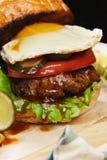 Hamburger met ei op een houten raadsclose-up Royalty-vrije Stock Foto's
