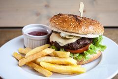Hamburger met kaas en gebraden gerechten en een ketchup royalty-vrije stock foto