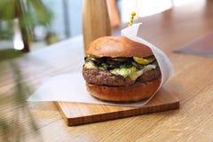 Hamburger met kaas en groene groenten en salade stock foto