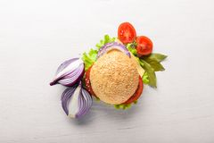 Hamburger met kaas, vlees, tomaten en uien en kruiden Royalty-vrije Stock Foto's