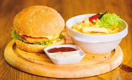 Hamburger met kaasvlees en salade Bedrieg maaltijd Heerlijke hamburger met sesamzaden Hamburgermenu Hoge caloriesnack royalty-vrije stock fotografie
