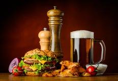 Hamburger met koude bier en gebraden gerechten Stock Afbeelding