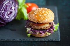 Hamburger met purpere kool over zwarte geweven raad Stock Fotografie