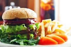 Hamburger met tomaat en aardappels Stock Foto's