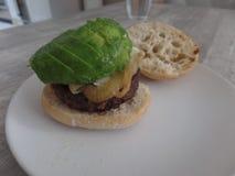 Hamburger met uien en gesneden avocado op een ciabattabroodje royalty-vrije stock fotografie