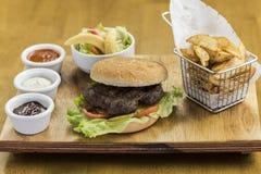 Hamburger mit gebratenen Kartoffeln und Salat stockbilder
