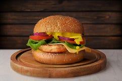 Hamburger mit Hühnertreffen, -gemüse und -senf auf hölzernem Hintergrund Lizenzfreie Stockfotografie