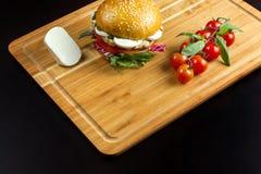 Hamburger mit Käse auf einem Bambusschlag Stockbild