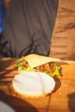 Hamburger mit Käse und einem Brötchen in der Küche Lizenzfreie Stockfotos