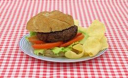 Hamburger mit Kopfsalattomatechips Stockbild