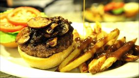 Hamburger with mushrooms and dripping gravy stock video footage
