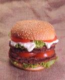 Hamburger na burlap workowym tle. Zdjęcie Stock
