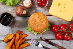 Hamburger near fresh vegetables. Royalty Free Stock Photos