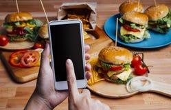 Hamburger - neemt de Gebruiks mobiele telefoon een foto Stock Afbeelding