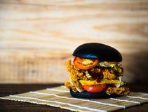 Hamburger nero su fondo di legno Fotografia Stock Libera da Diritti