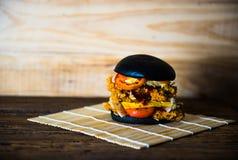 Hamburger nero su fondo di legno Fotografia Stock