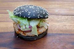 Hamburger noir avec du porc et la sauce épicée Image libre de droits