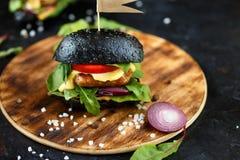 Hamburger noir avec la côtelette, les verts, le fromage, les oignons et les tomates d'un plat en bois sur une table foncée photographie stock libre de droits