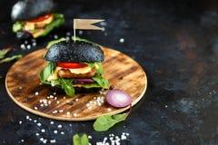 Hamburger noir avec la côtelette, les verts, le fromage, les oignons et les tomates d'un plat en bois sur une table foncée photo stock