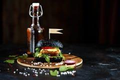 Hamburger noir avec la côtelette, les verts, le fromage, les oignons et les tomates et une bouteille de bière d'un plat en bois s images stock