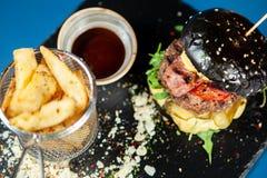 Hamburger noir avec le petit pâté de boeuf juteux, chees, pommes frites Images stock
