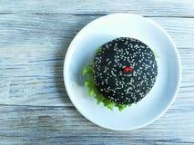 Hamburger noir avec le spaciou sous forme de coeurs sur le fond en bois blanc Images stock