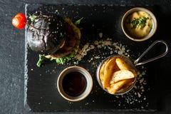 Hamburger noir délicieux de boeuf avec le soia SOS et les pommes frites Photo stock
